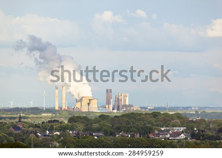 View from a slag heap over rural landscape to a distant steaming coal-fired power station surrounded by wind turbines. - stock photo