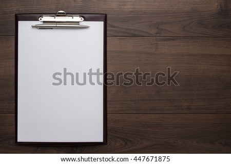 view from above. brown wooden office table with notepad and pen - stock photo