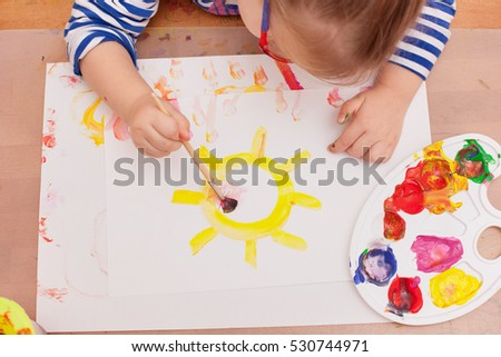 view from above. child draws a brush and paints on white paper