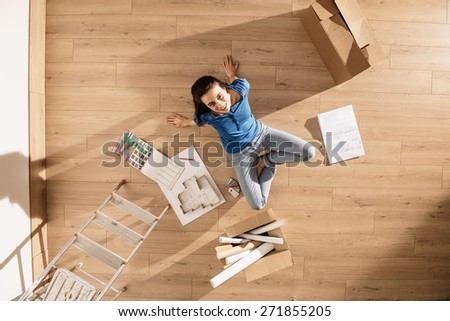 view from above, looking at the camera a young woman sitting on the floor of her new home, there are blueprints and samples colors to help her to think about her new interior decoration - stock photo