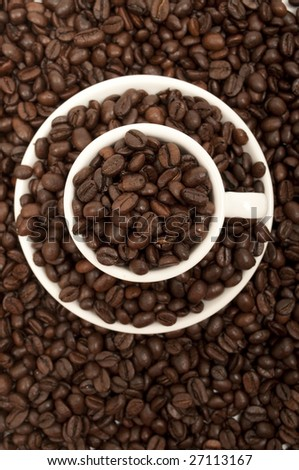 view from above of a cup surrounded by and filled with coffee beans