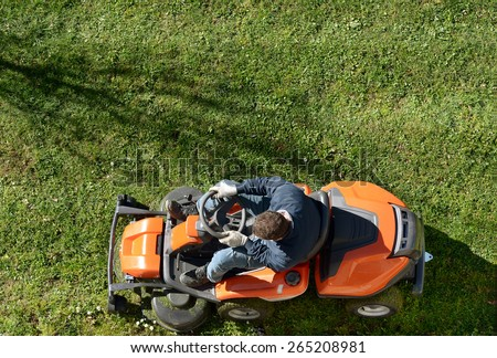 View from above of a man mowing a lawn on an orange ride-on mower as he attends to yard maintenance - stock photo