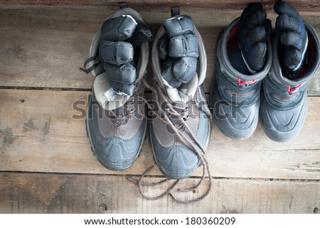 View from above of a pair of adult snow boots alongside those of a child on the wooden floor of a cabin each with a pair of gloves inside ready to be worn to go out into the cold winter weather - stock photo