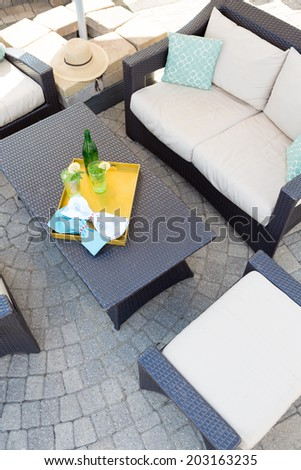 View from above of a vacant upmarket outdoor patio with modern garden furniture with comfortable upholstered cushions on paving with a central table with a tray of chilled drinks - stock photo