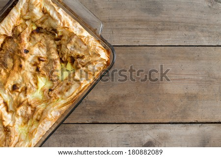 View from above of an uncut fresh homemade Turkish borek in an oven dish standing on an old wooden table in a rustic kitchen, with copyspace