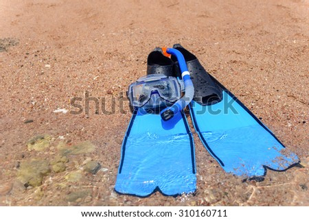 View from above of blue rubber flippers and snorkel lying on a sandy beach ready to go skin diving on a summer vacation - stock photo