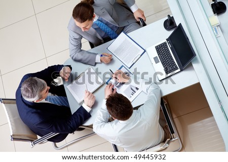 View from above of business men sitting at table in the office and discussing new plan - stock photo