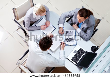 View from above of business team sitting at table in the office and communicating with each other - stock photo
