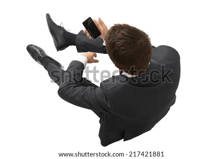 view from above of businessman in black suit with cellphone sitting on the floor. isolated on white background