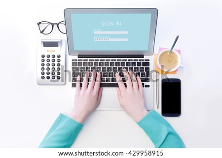 View from above of businesswoman sitting at desk and checking e-mails on her laptop. Isolated on white background. - stock photo