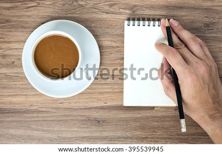 View from above of coffee cup and notebook and hand holding pencil on the wooden office desk table