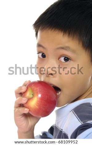 View from above of cute schoolboy with and apple looking at camera - stock photo