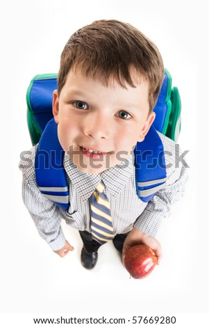 View from above of cute schoolboy with backpack and apple looking at camera - stock photo