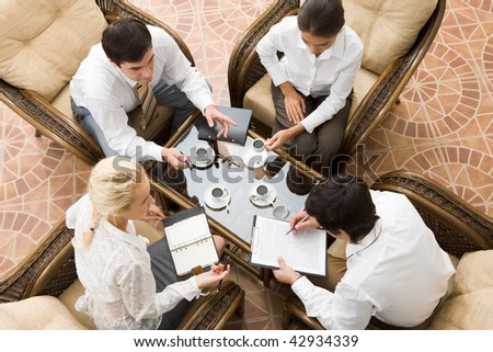 View from above of four businesspeople discussing work - stock photo