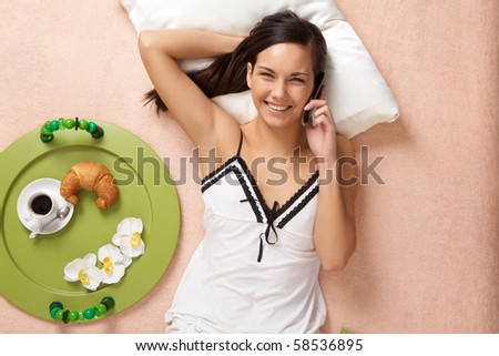 View from above of happy girl speaking on cellular phone on bed - stock photo