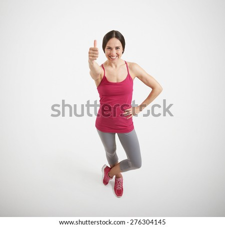 view from above of happy woman in sport wear showing thumbs up and smiling over light grey background - stock photo
