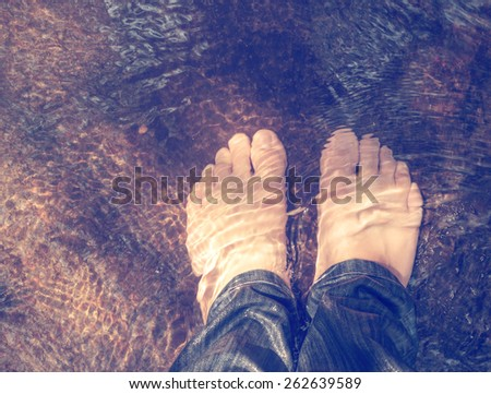 View from above of man feet underwater vintage color tone effect - stock photo