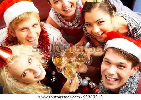 View from above of merry friends with flutes of champagne looking upwards