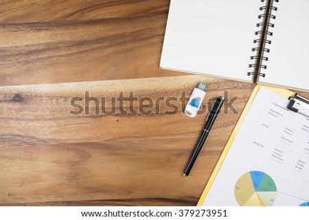 View from above of office supplies and   analyze business chart on a wooden working table background. - stock photo