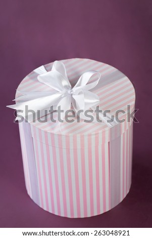 View from above of pink and white striped gift box with white bow - stock photo