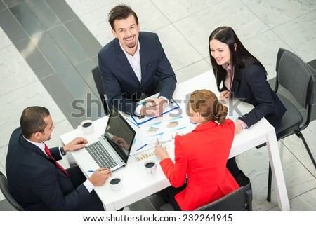 View from above of several business people are planning work at round table. - stock photo