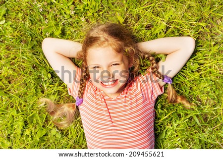 View from above of smiling girl laying on  grass - stock photo