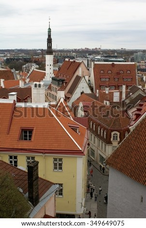 View from above of Tallinn, Estonia, showing red roofs and buildings in the old walled city, with church spire protruding above roof line - stock photo