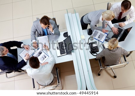 View from above of two business teams working separated by border in office - stock photo