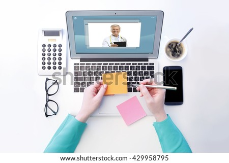 View from above of young woman sitting at desk in front of laptop and having video chat with senior male doctor. Isolated on white background. - stock photo
