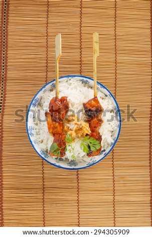 View from above on a bowl of rice with two grilled pork skewers - stock photo