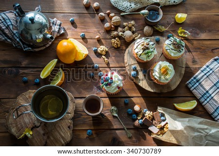 view from above on a wooden table with cupcakes, berries, candies, chocolate, nuts and tea set - stock photo