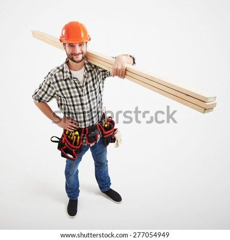 view from above on smiley builder in uniform holding long wooden boards. isolated on light grey background - stock photo