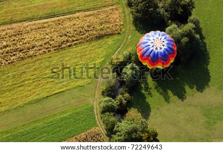 View from above on the hot air balloon flying over the fields and creek. - stock photo