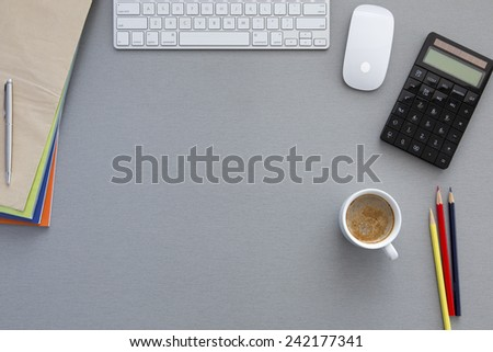 View from above on the office working place at morning. Well organized workspace on the grey wooden table with keyboard, pens, coffee mug and other business supplies - stock photo
