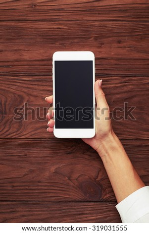 view from above on womans hand with smartphone over wooden background - stock photo