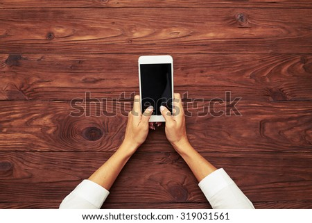 view from above on womans hands typing on smartphone over wooden brown table - stock photo