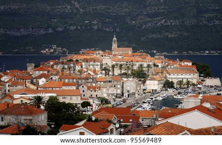 View from above to the ancient Korcula town in Croatia and mountains in background - stock photo
