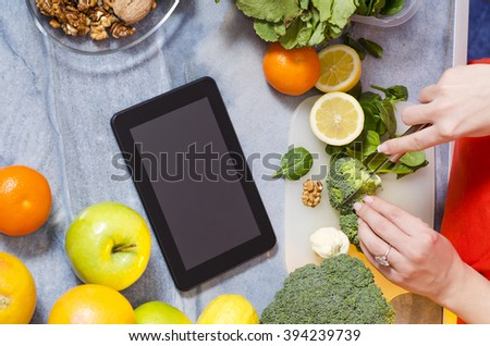 View from above young woman chopping broccoli and young spinach, tablet in the middle of modern marble slab. Healthy food an recipes concept. Selective focus on right side of image  - stock photo