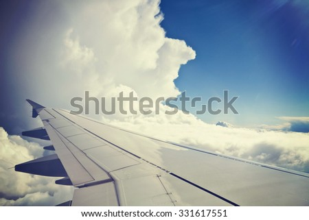 View from airplane, carrier wing and beautiful cumulus of white clouds against blue sky, grunge effect Instagram-like added. - stock photo