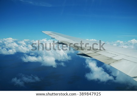 View from airplane window. Wing of an airplane flying above the clouds over tropical island