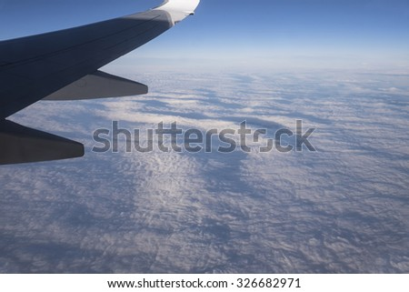 View from airplane window with blue sky, white clouds and wing - stock photo