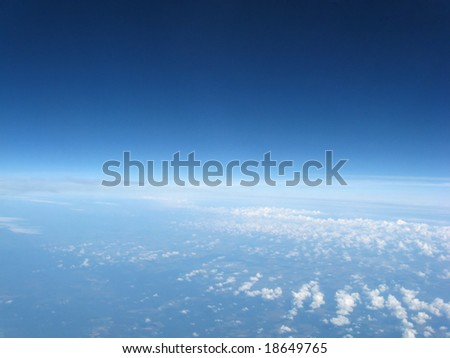 View from an airplane high above the clouds - stock photo