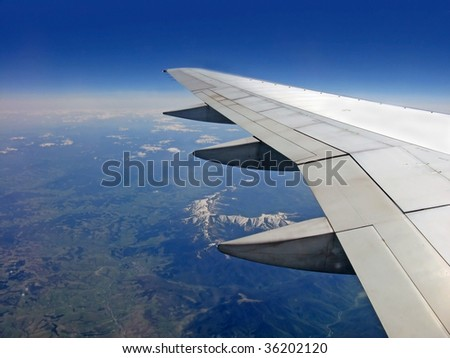 view from an airplane illuminator with earth and wing - stock photo