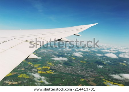 View from an Airplane Window of a Wing, Sky and Land - stock photo