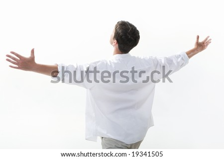 View from aside of happy young man raising his arms enjoying life