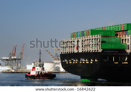 View from behind as a red tugboat pulls a massive merchant vessel around in a narrow harbor channel, with loading cranes in the background.