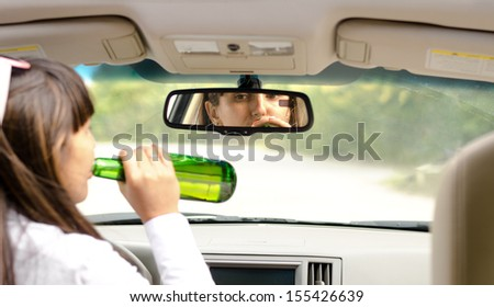 View from behind inside a car of a woman driver drink driving lifting the bottle to her lips and gulping down the alcohol as she steers the car - stock photo