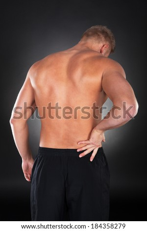 View from behind of a shirtless strong muscular man with backache clutching his lower back with his hand - stock photo
