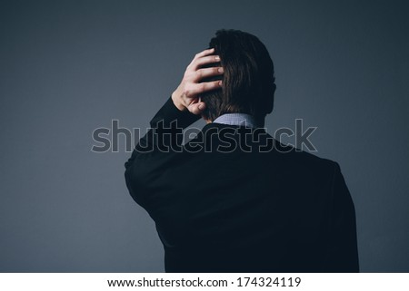 View from behind of a stylish businessman standing with his hand to his head as he scratches it in perplexity or as he nurses a throbbing headache on a dark grey background
