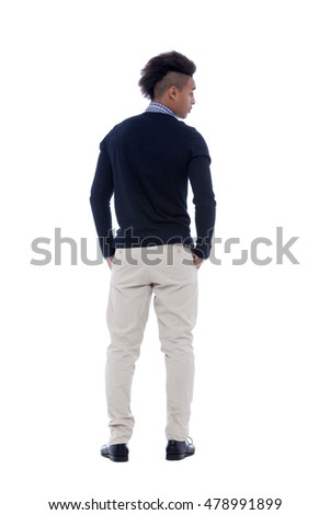 View from behind of a young african man standing relaxed with hands on pocket.